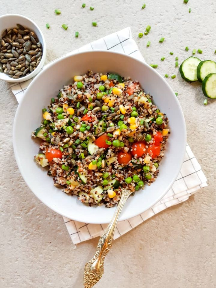 Quinoa salad in a deep plate with a spoon