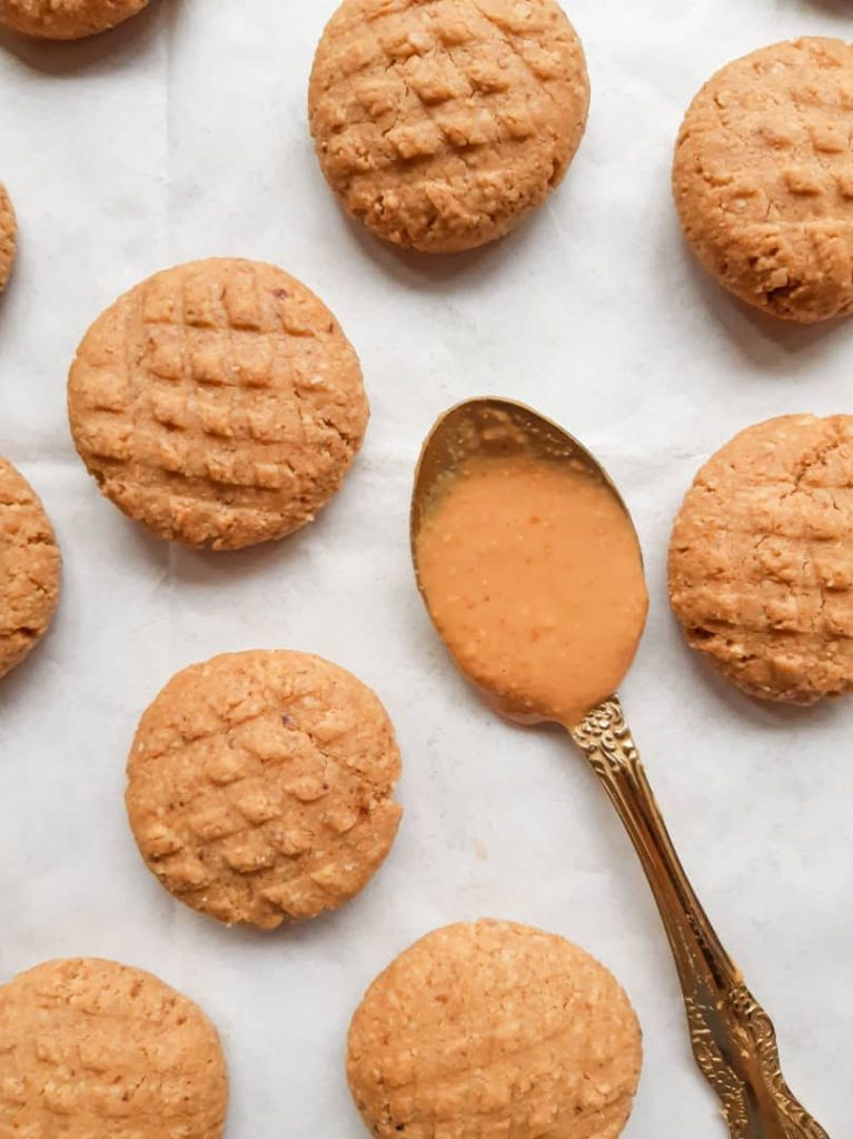 Peanut butter cookies arranged randomly on a white background with a spoonful of peanut butter at the middle