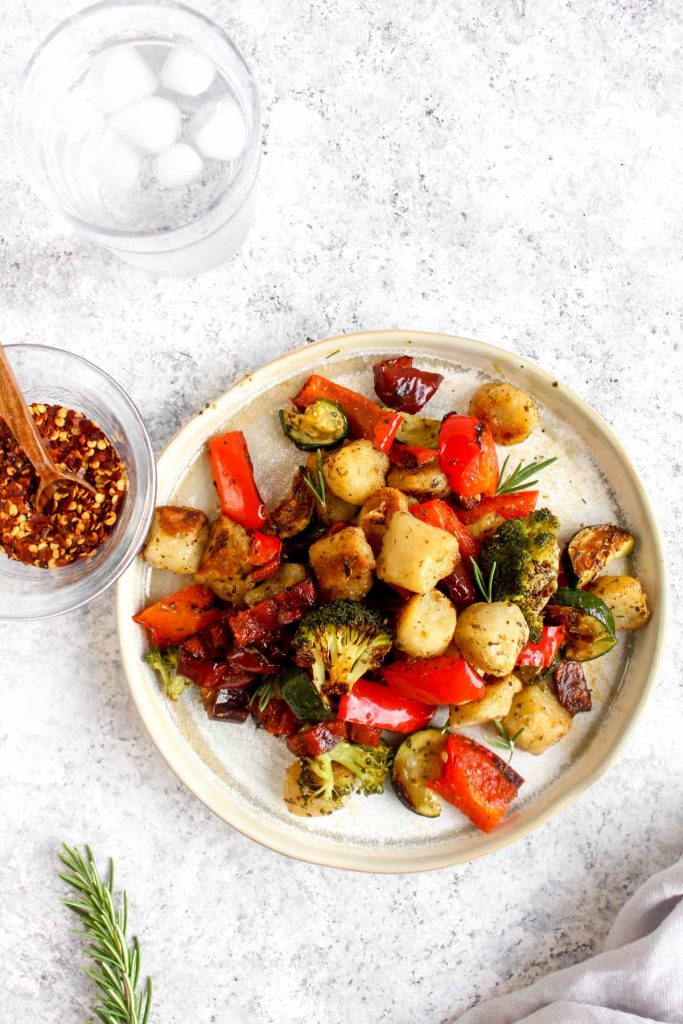 Cauliflower gnocchi with roasted vegetables served on a white plate
