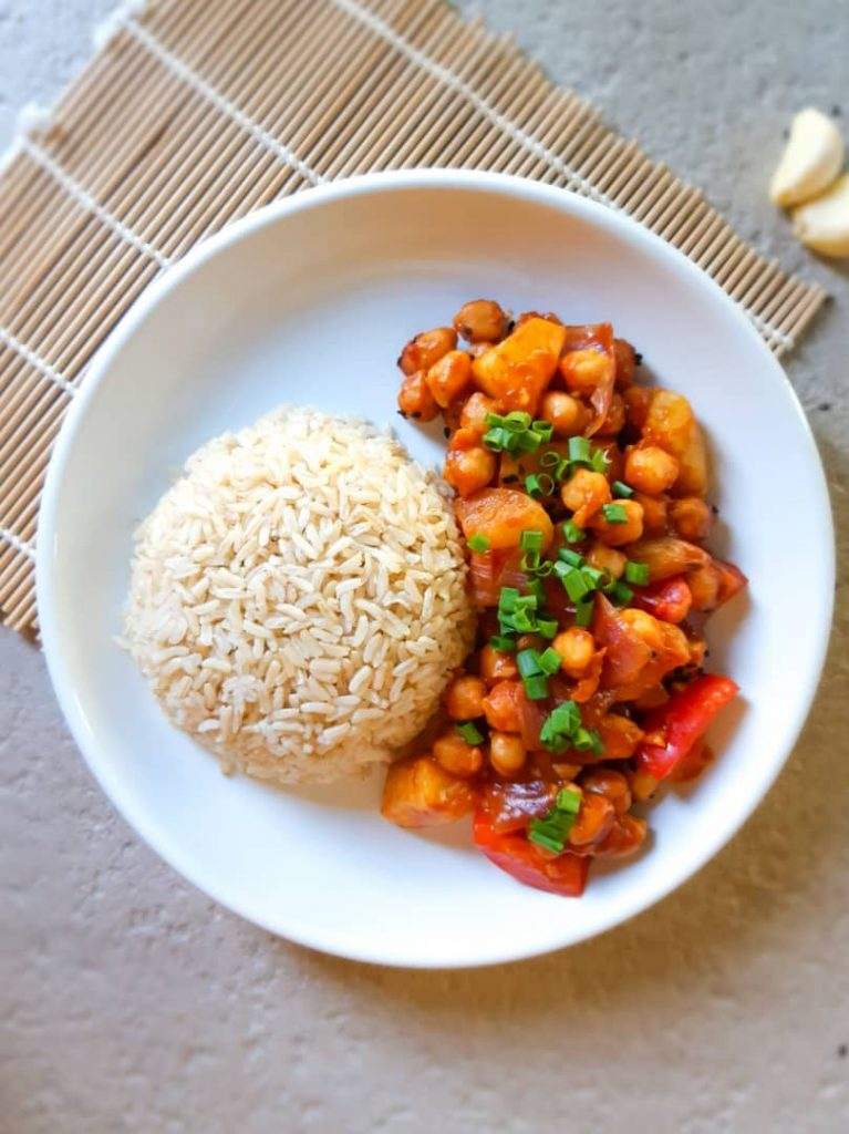 Sweet and sour chickpeas served with some brown rice on a white plate