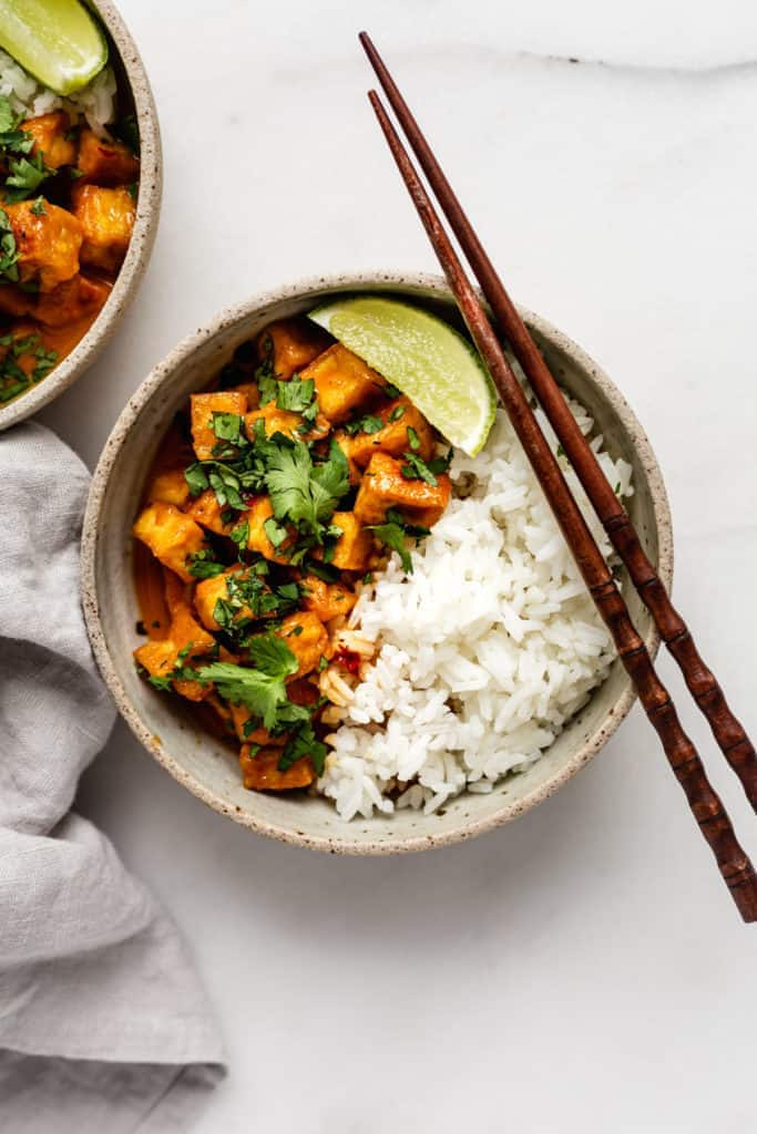 Thai coconut curry tofu served with a side of rice in a bowl