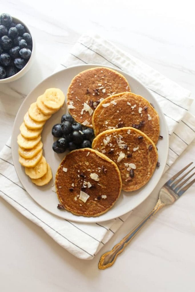 An overhead shot of vegan pancakes with sliced bananas and blueberries on the side