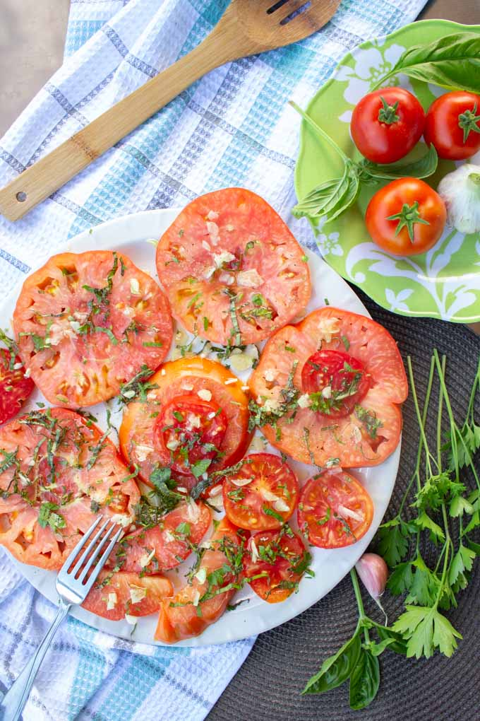 Sliced tomatoes salad served on a white plate. There are some fresh tomatoes and herbs on the side as decoration