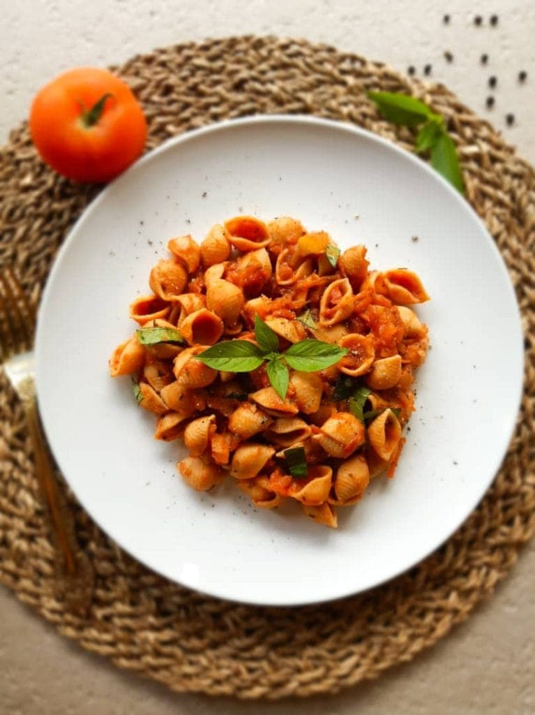 An overhead shot of tomato pasta on a white plate