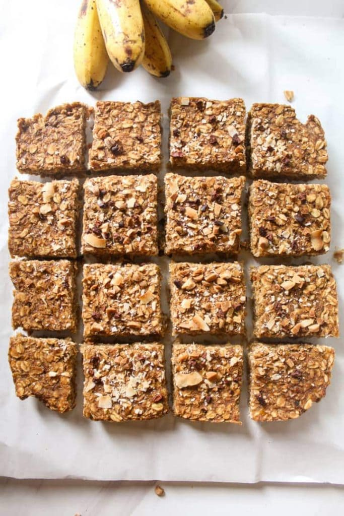 An overhead shot of oatmeal breakfast bars with a bunch of bananas in the background