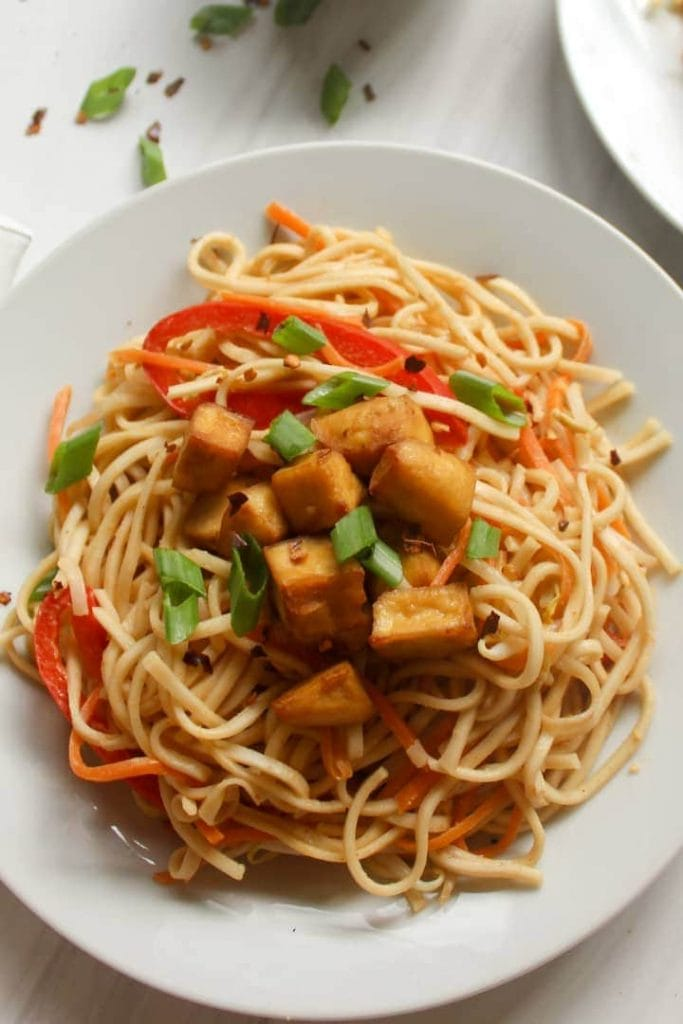 A close up shot of peanut noodles served on a white plate and topped with tofu and scallions.