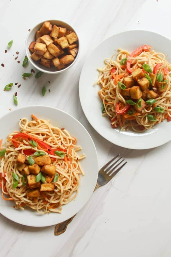 2 plates of peanut noodles topped with baked tofu. There is a bowl of baked tofu between them