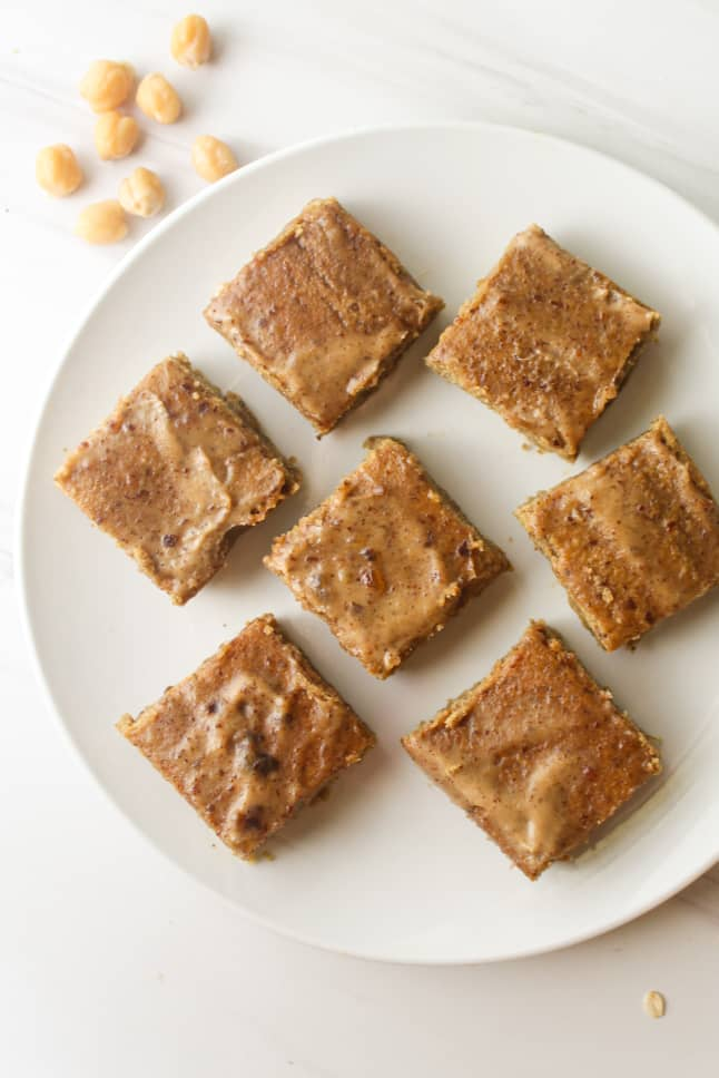 Blondies arranged on a white plate. There are some chickpeas scattered in the background.