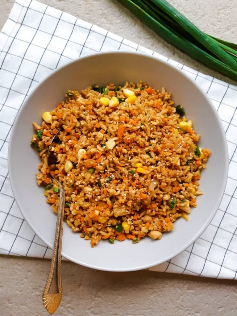 Fried rice served in a deep plate. There is a spoon sticking into the fried rice