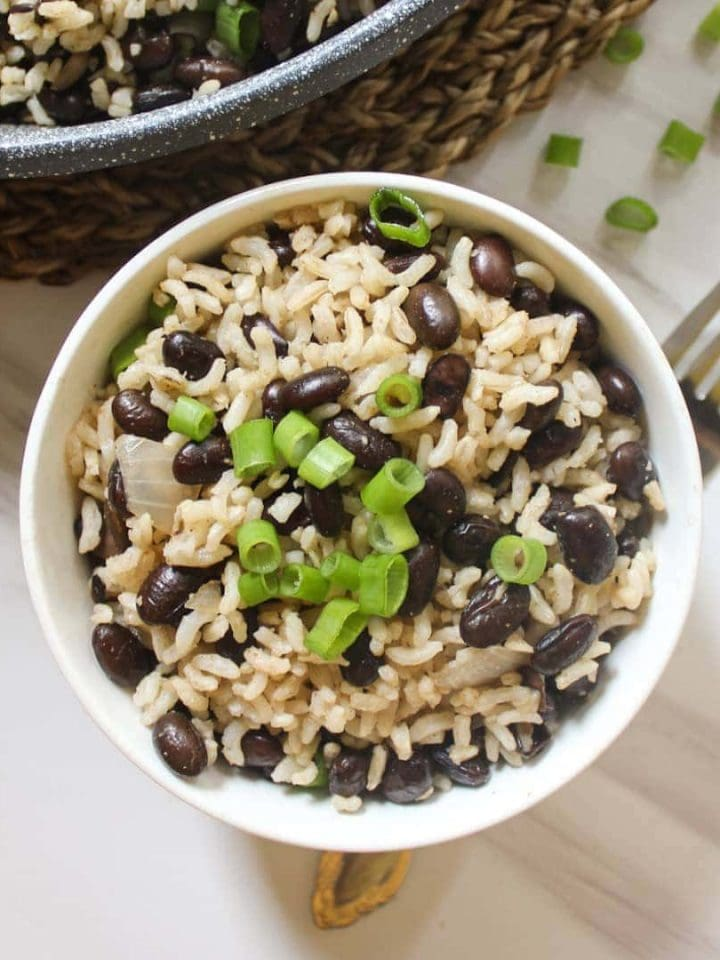 A close up shot of rice and beans served in a white bowl