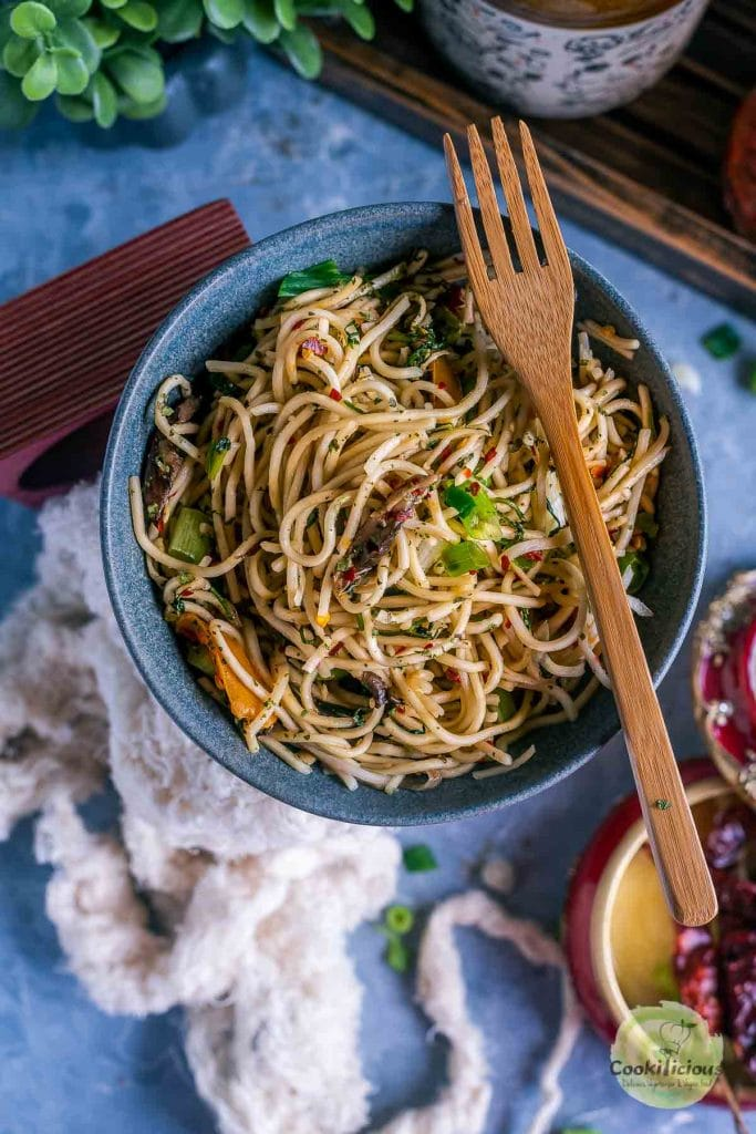 Noodles served in a blue bowl with a wooden spoon on it.