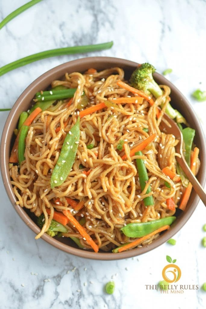 Chow mein served in a brown bowl with a stalk of scallion in the background