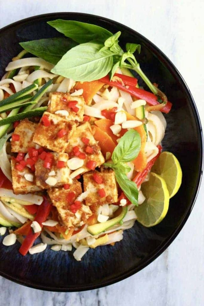 Vegan pad thai served in a black bowl topped with tofu slices