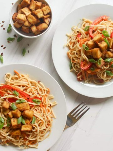 2 plates of noodles served with tofu