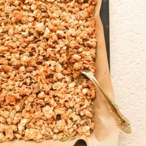 Granola in a baking tray with a spoon spooning out some granola