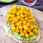 Avocado toast topped with chickpeas served on a wooden chopping board