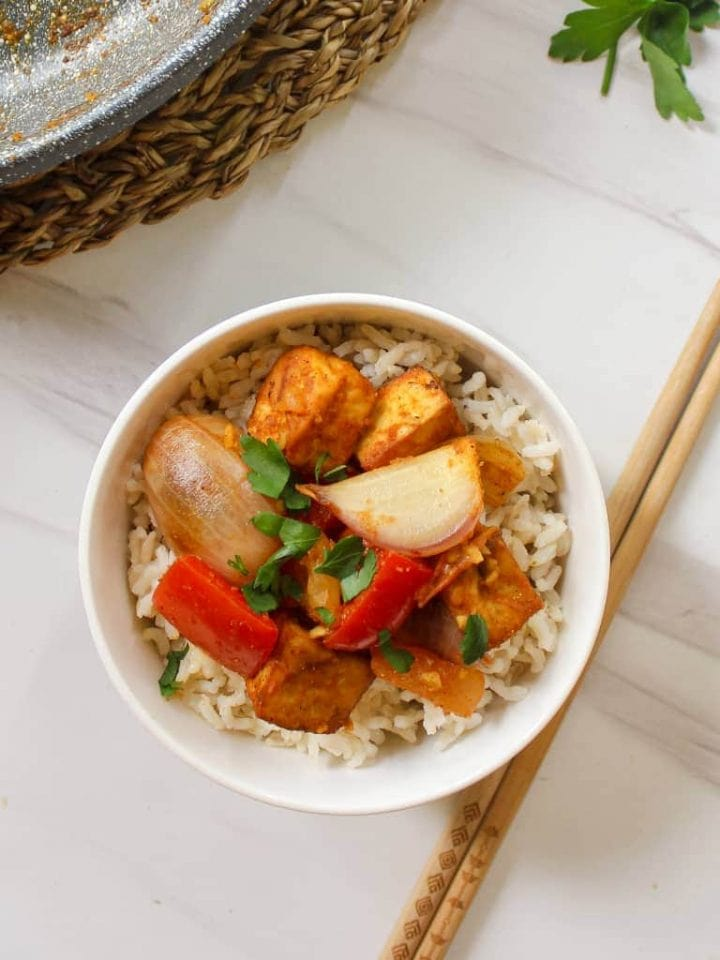 Stir-fry served with some brown rice in a white bowl
