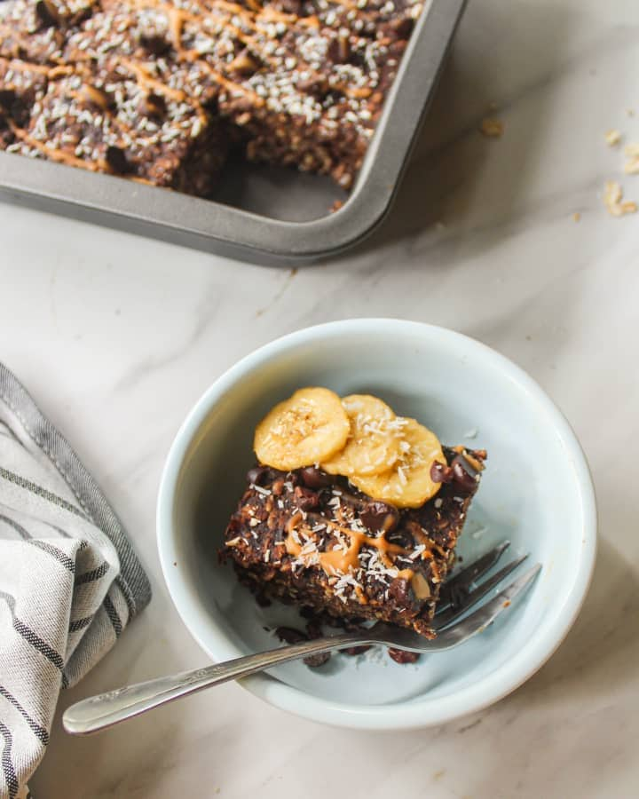 A square of oatmeal in a blue bowl topped with sliced bananas and fork on the side.