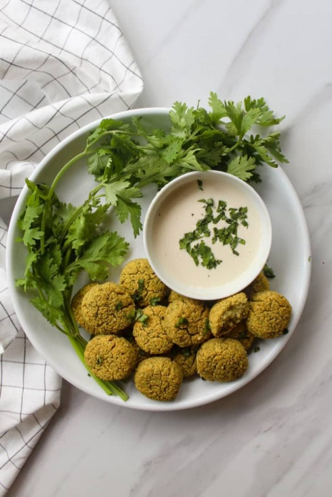 Falafels arranged on a white plate with a bunch of parsley and a side of tahini sauce
