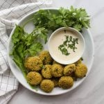 Falafels and a bunch of parsley in a white plate with some tahini sauce