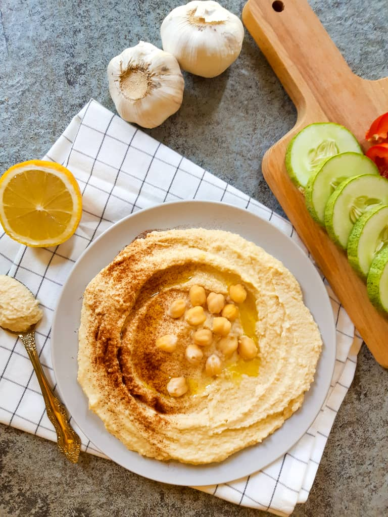 Hummus served on a purple plate topped with chickpeas. There is a spoon, some chopped vegetables, half a lemon and some whole garlic in the background