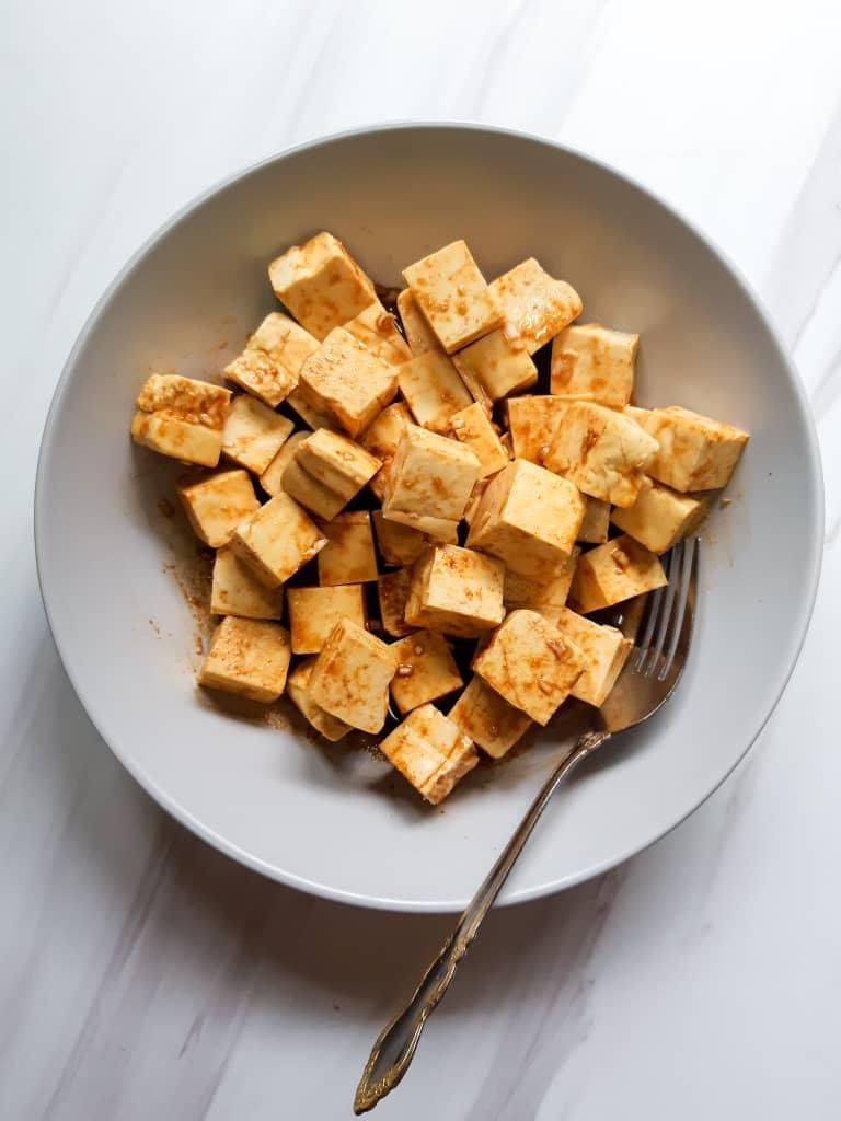 Tofu cubes marinating in a purple deep dish
