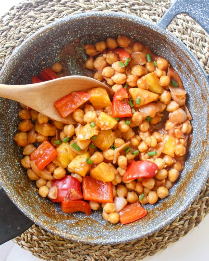 Sweet and sour chickpeas in a marble pan with a wooden spatula sticking into it