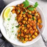 Chana Masala served with some rice in a white bowl