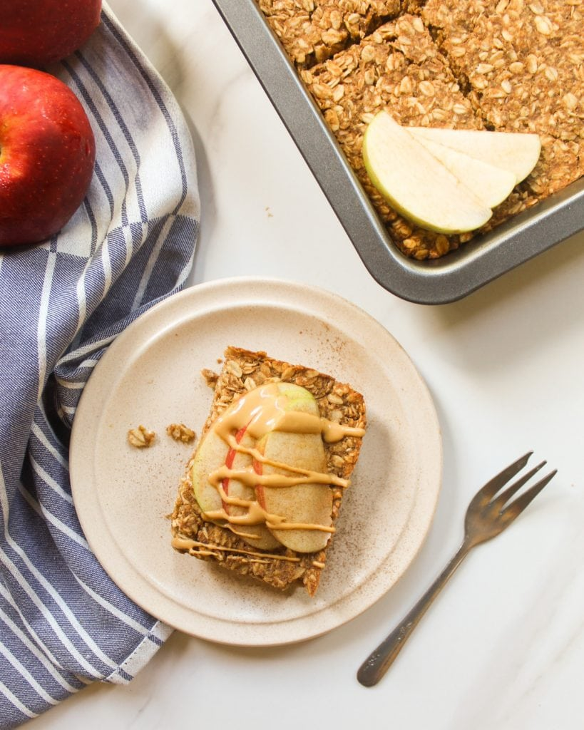 A slice of baked oatmeal served on a side plate topped with apple slices and peanut butter. There is a small fork beside it