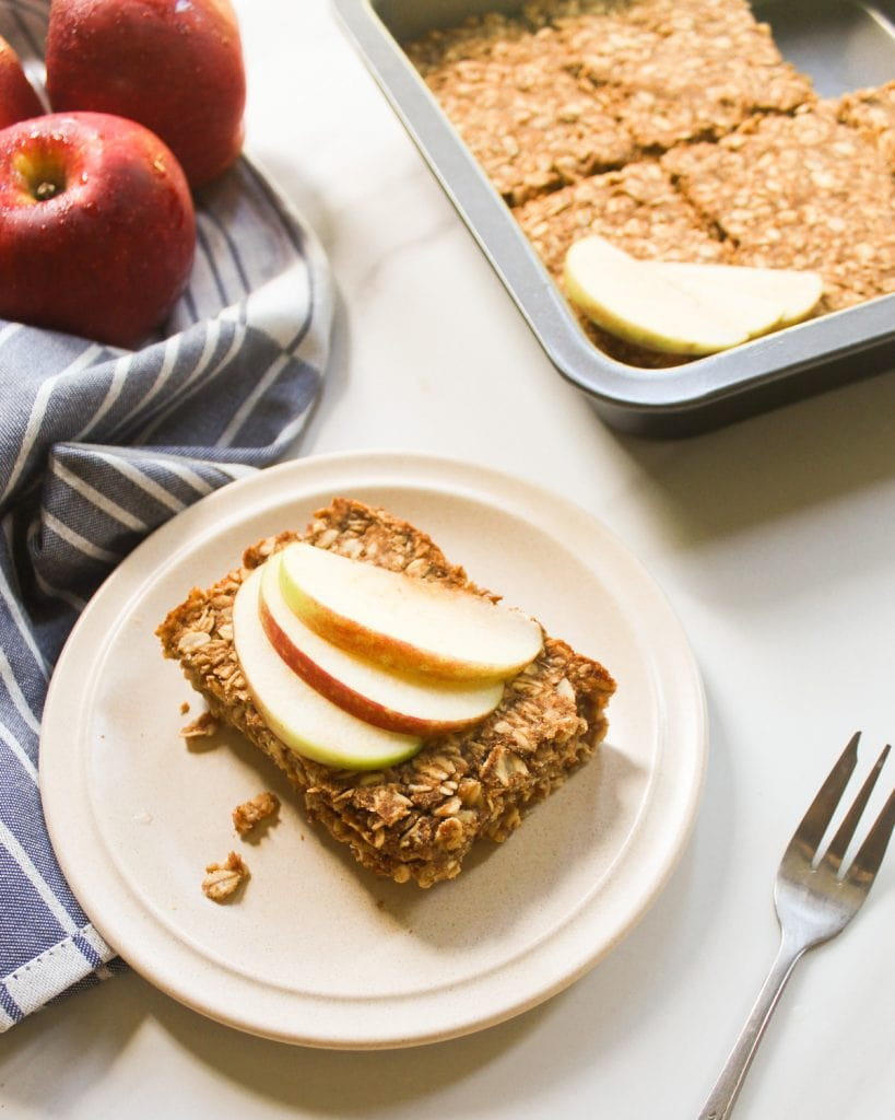 A side view of baked oatmeal serve on a small plate topped with apple slices.