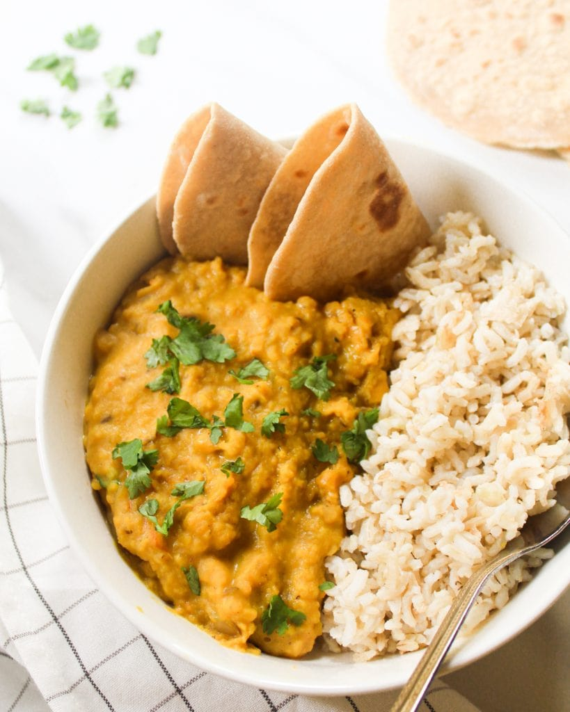 Close up shot of dal served with folded chapati and brown rice.