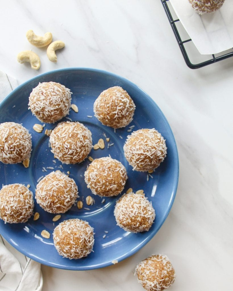 Date balls arranged in a blue side plate with some cashews and cooling tray in the background