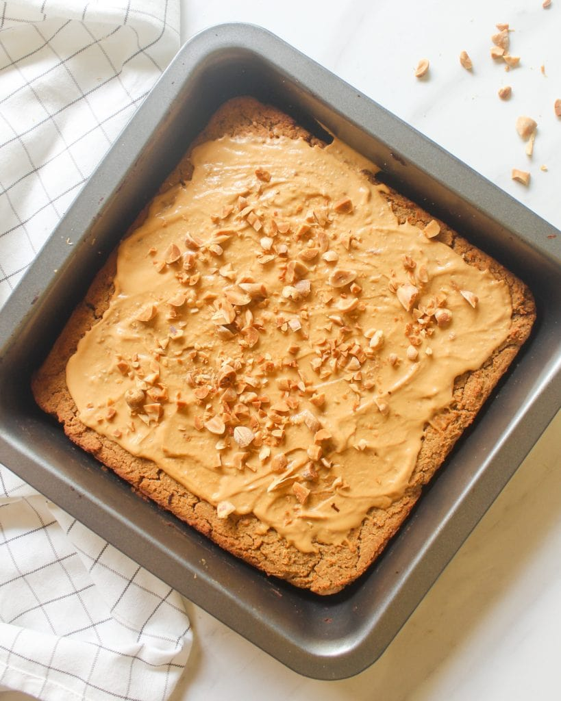 Blondies in a black sqaure baking pan topped qith peanut butter and chopped peanuts