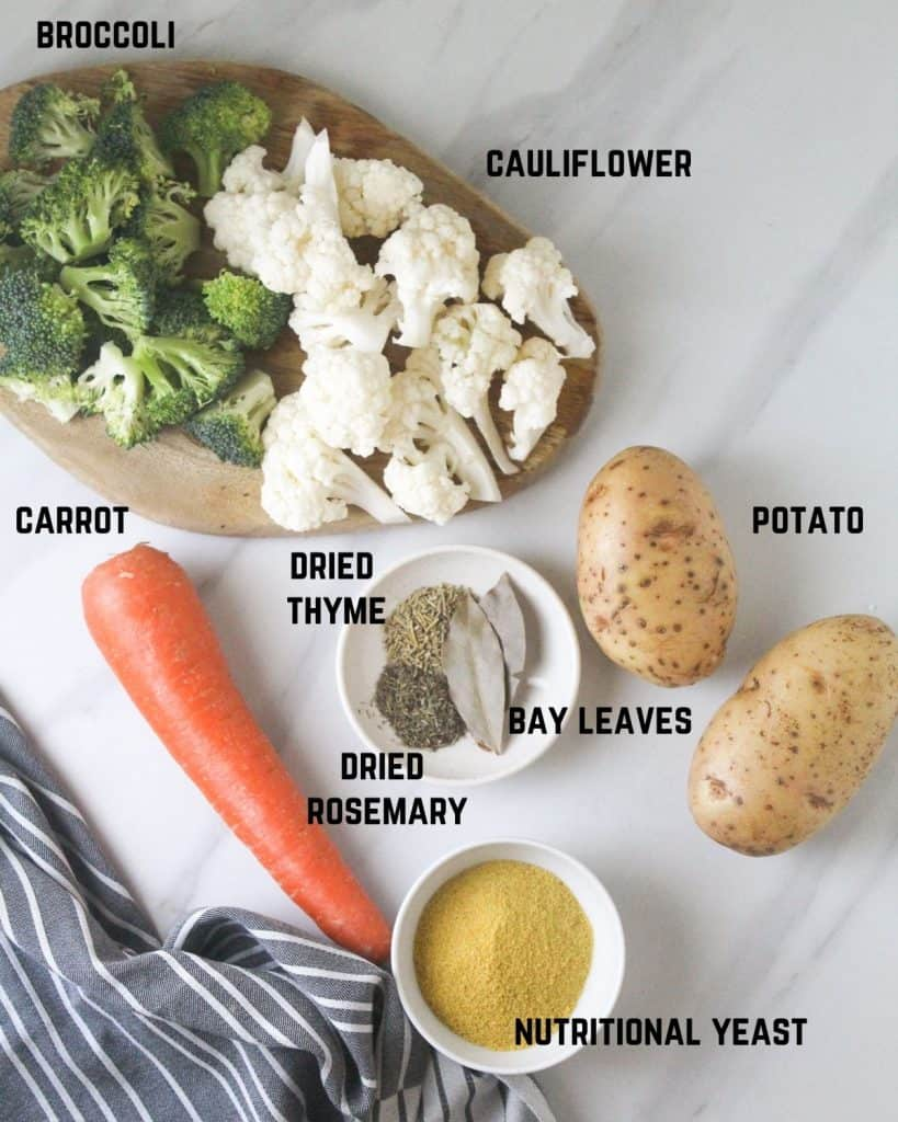 Ingredients needed for soup like carrot, broccoli, cauliflower, potato, dried thyme, dried rosemary, bay leaves and nutritional yeast