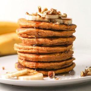 A stack of pancakes topped with banana slices and chopped pecans with a drizzle of maple syrup dripping down it.