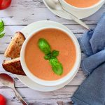 Tomato bisque served in a white bowl topped with basil leaves.