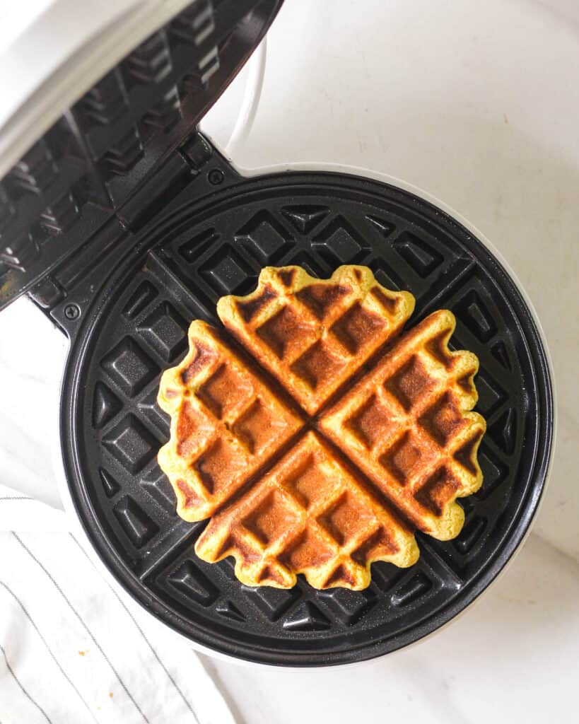 A freshly made waffle in a Belgium waffle maker.