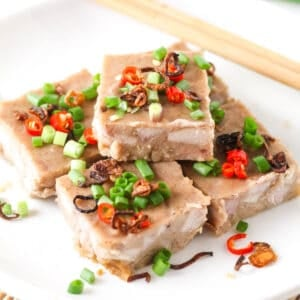A close-up look of a few slices of yam cake arranged on a white plate topped with chopped green onion, sliced chili and fried shallots.