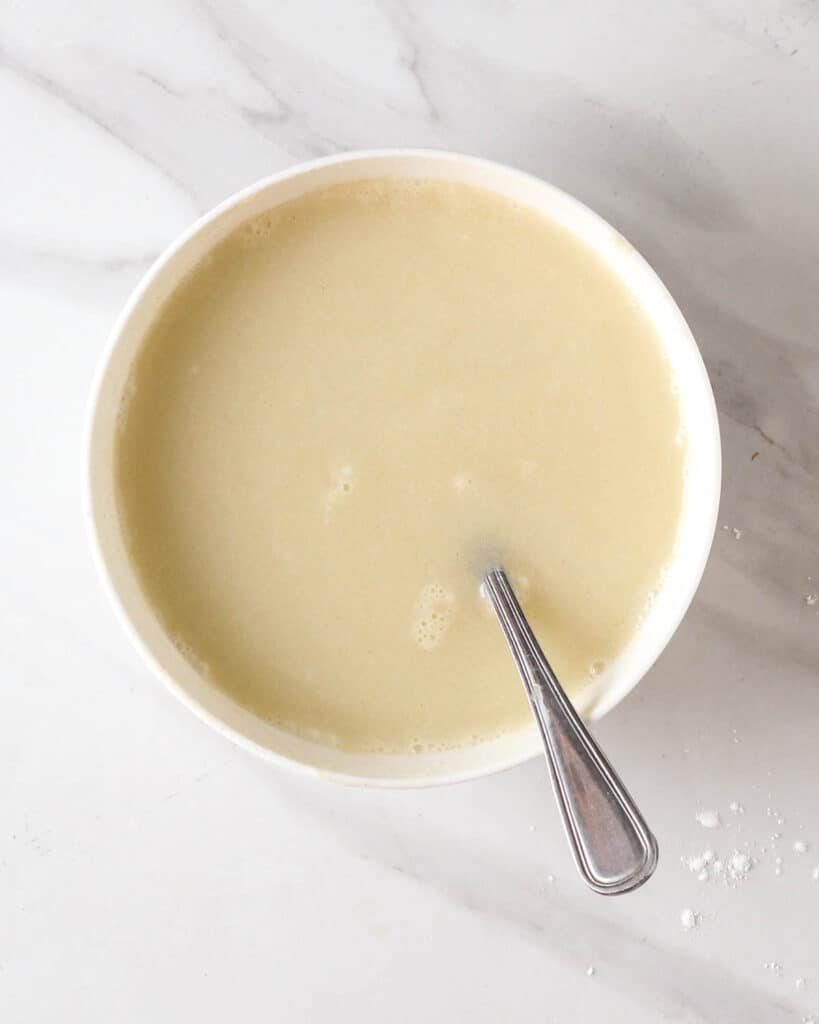 Mixing all flours together with water in a white bowl.
