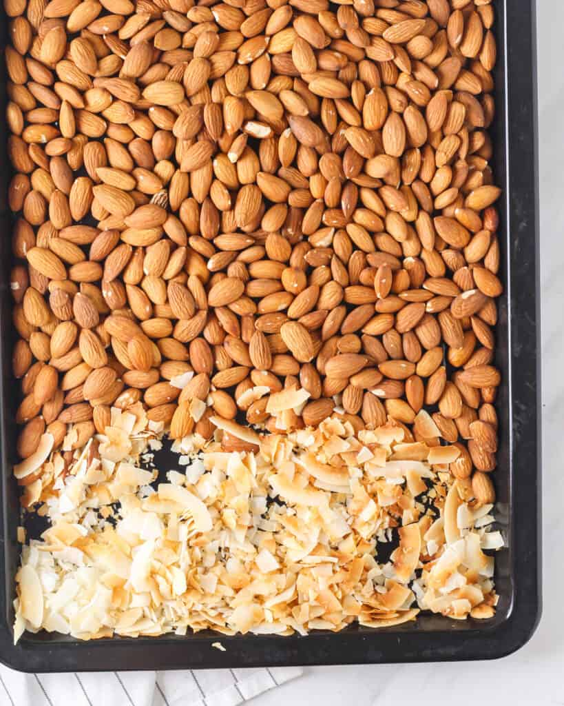 Toasted almonds and coconut flakes in a black baking tray