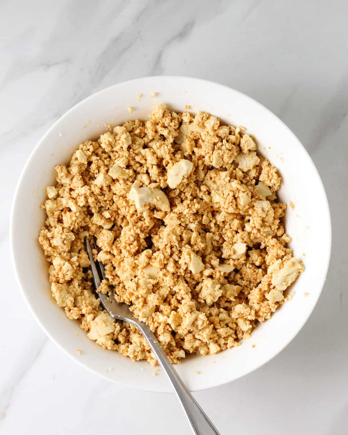 Seasoned crumbled tofu in a bowl with a fork