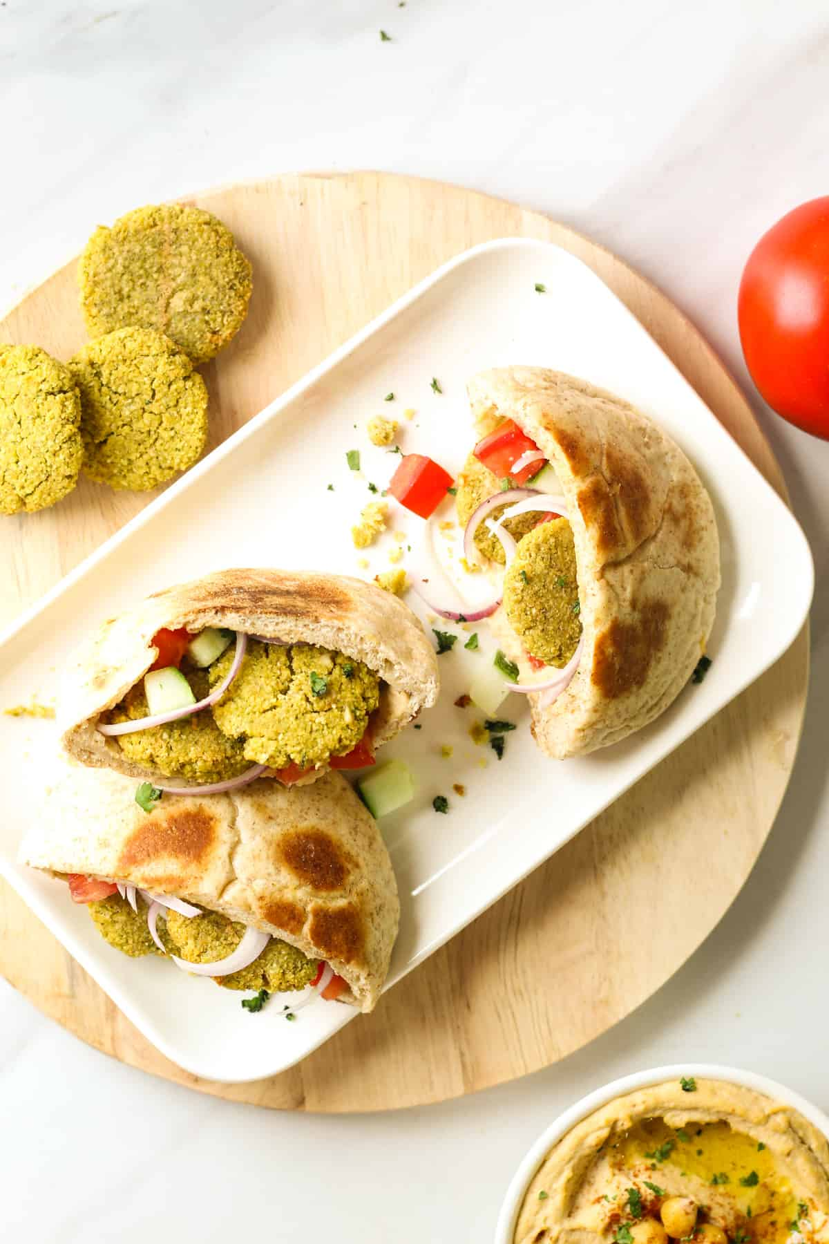 An overhead shot of 3 stuffed pitas arranged on a white rectangular plate that is place on a round wooden chopping board