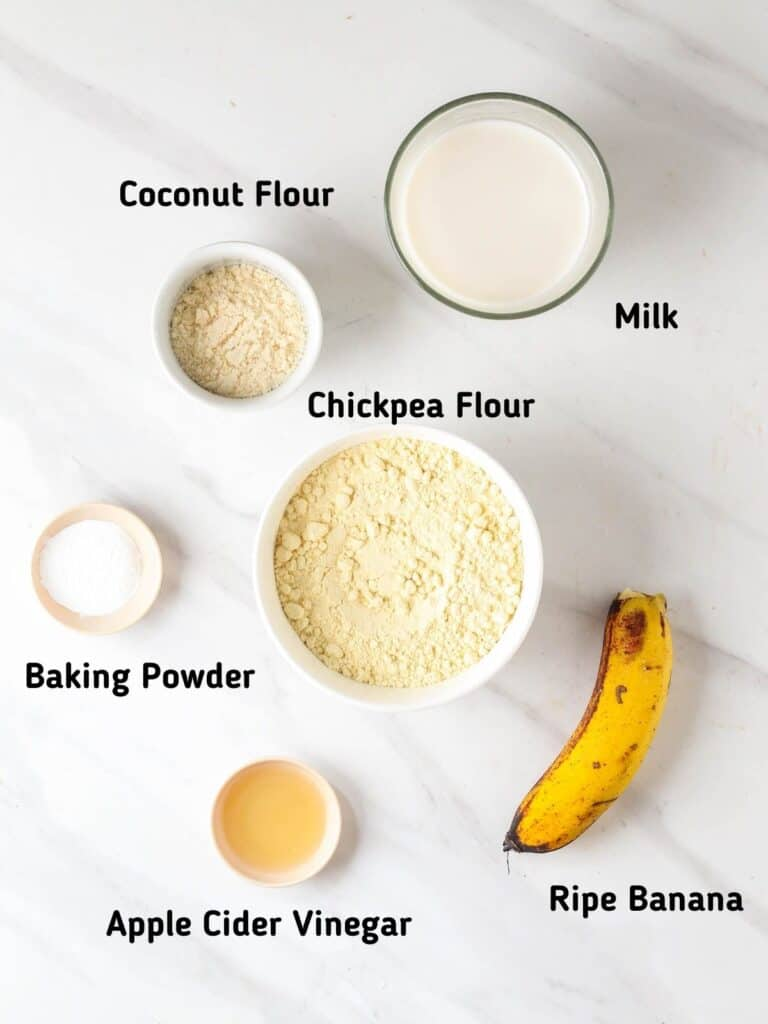 Ingredients needed for this recipe like coconut flour, chickpea flour, milk, baking powder, apple cider vinegar and banana.