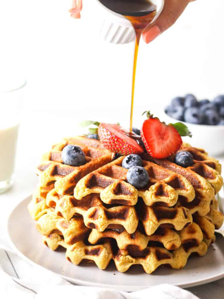Pouring maple syrup over a stack of vegan protein waffles that are topped with fresh berries.