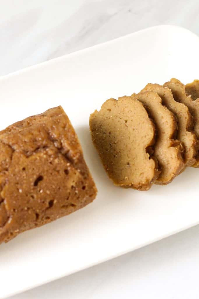 Overhead shot of seitan slices on a white rectangular plate