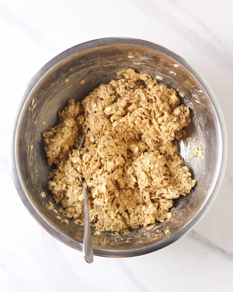 Batter of oatmeal bars in a mixing bowl with a fork