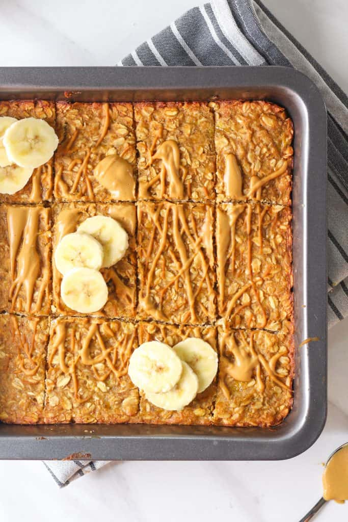 Close-up of oatmeal bars in black square baking pan.