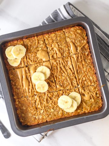Oatmeal bars in a black square baking pan topped with peanut butter and sliced bananas