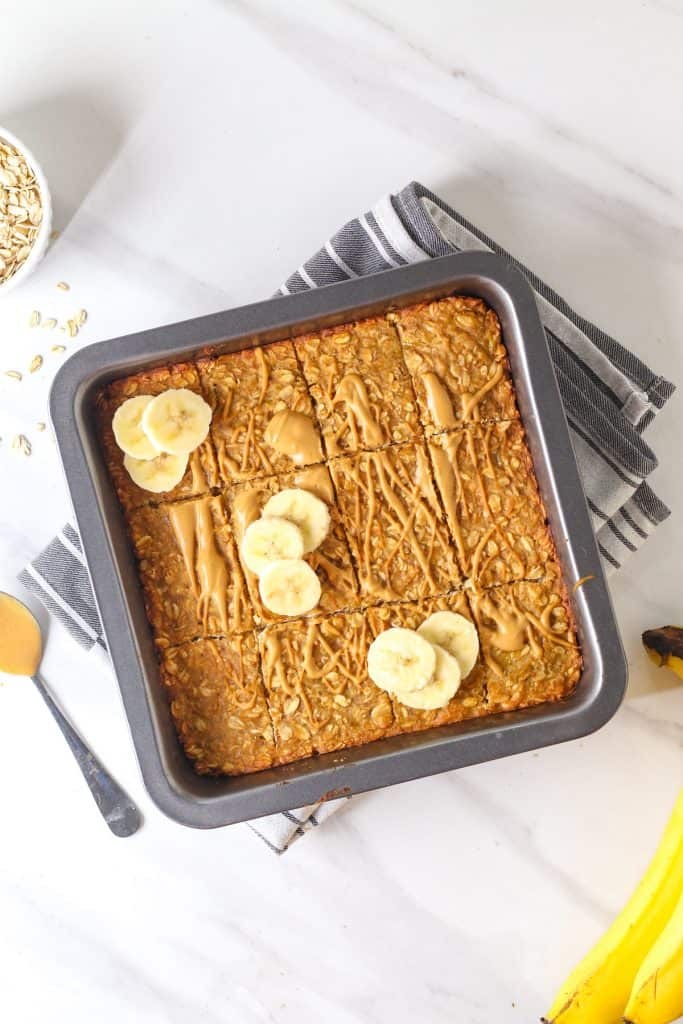 Oatmeal bars in a black square pan drizzled with peanut butter and topped with banana slices.