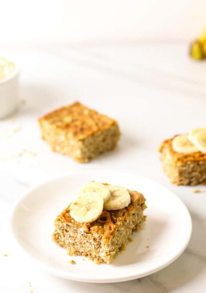 A slice of oatmeal bars on a white plate topped with banana slices